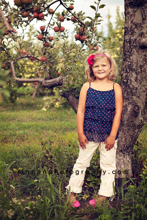 girl standing up against tree at apple hill orchard